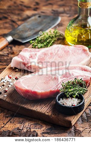 Raw pork meat chopes with herbs, oil and spices on wooden background.
