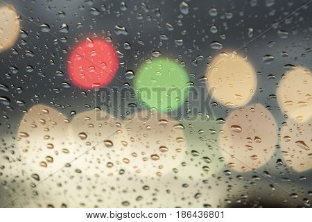 Rain drops on window with road light bokeh, City life in night in rainy season abstract background,water drop on the glass, night storm raining car driving concept.