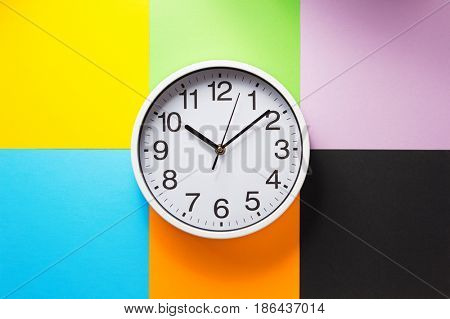 wall clock at abstract colorful paper background texture