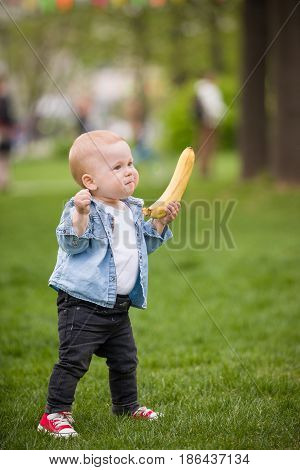 Cute little toddler boy with banana walking in the park on a summer day. First baby's steps. Outdoor. Child taking first steps on the green grass.