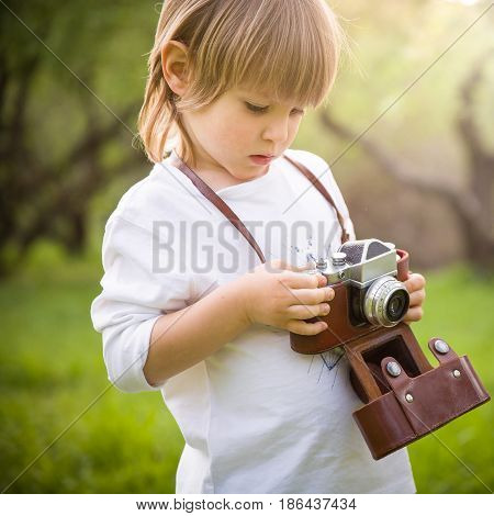 Adorable little kid boy with retro photo camera standing in the green park on s sunny day. Outdoors. Young smiling photographer.