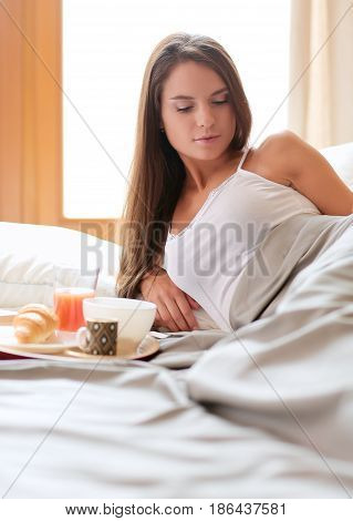 Breakfast in bed with coffee and croissant for attractive young woman.