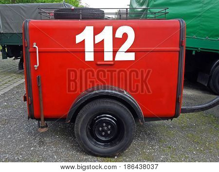 old red German fire department trailer with emergency phone number
