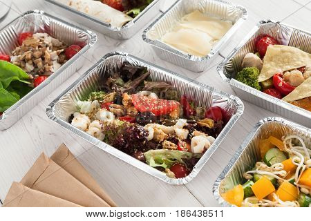 Healthy food background. Take away meals in foil boxes. Fitness nutrition, colorful vegetable salads and fruits. Top view, flat lay.