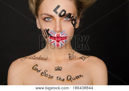 Portrait of woman with english symbols on her face black background