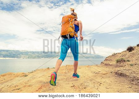 Woman running with backpack on rocky trail at seaside and mountains. Young woman training and trail running on mountain rocky dirt path looking at beautiful inspirational landscape view.