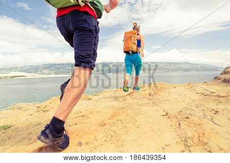 Couple runners running with backpacks on rocky trail at seaside and mountains. Young woman and man trail running on mountain path looking at beautiful inspirational landscape view.