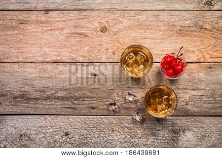 whiskey with ice in glassesand cherry on rustic wood background, top view with copy space