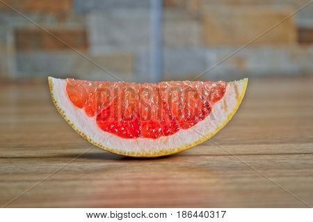 Closeup of a red grapefruit wedge on a wooden table