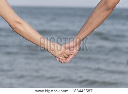 Happy couple holding hands on sea background.