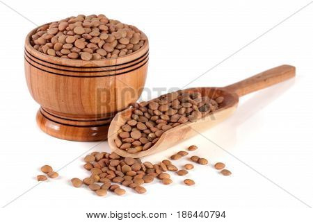 Lentils in a wooden bowl with a spoon isolated on a white background.