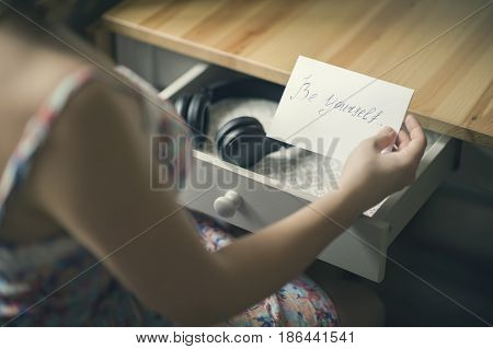 The girl with headphones and  message be yourself. The inscription on the paper be yourself. The concept of friendship and relationships.