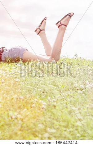 Low section of woman lying on grass against sky