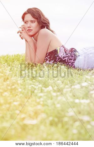 Side view of thoughtful young woman lying on grass against clear sky