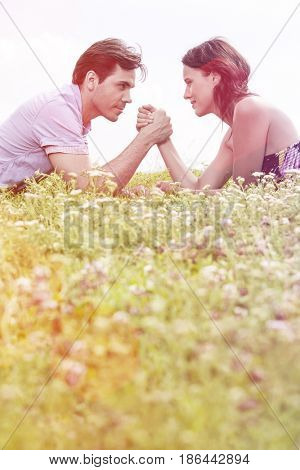 Profile shot of couple arm wrestling while lying on grass against sky