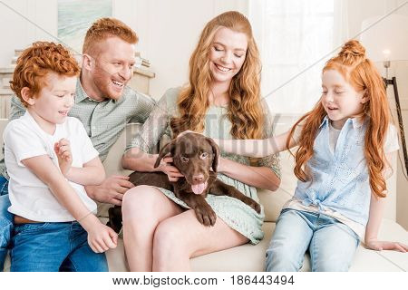 Front View Of Beautiful Redhead Family Playing With Puppy At Home, Family Fun At Home Concept