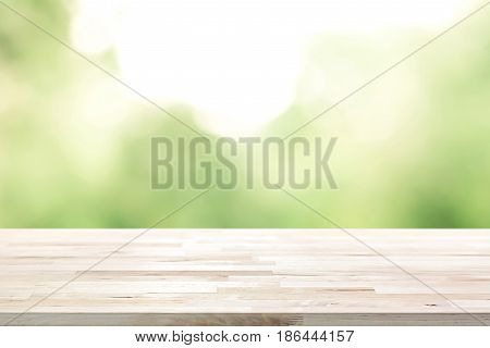 Wood table top on blur abstract natural green background - can be used for display or montage your products
