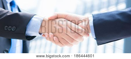 Close up of businessman hands making handshake panoramic banner