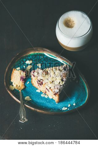 Dessert and coffee. Piece of lemon, ricotta, almond and raspberry gluten-free cake and glass of latte over dark wooden background, selective focus, copy space