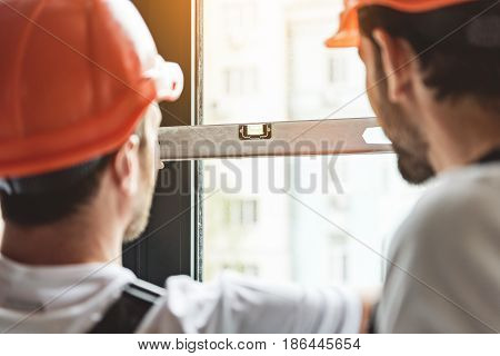 Constructors are holding building level and checking angle of deviation on window frame. They wearing hardhats