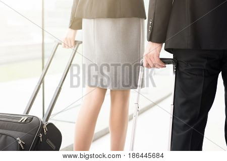 Business people (or flight attendants) pulling luggage while walking at the airport hallway