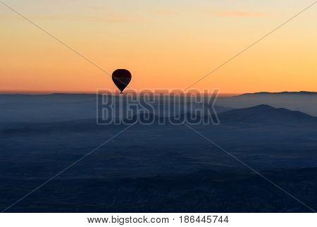 Hot Air Balloon Flying Over Valley At Sunrise. Cappadocia. Turkey