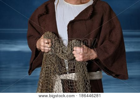 Biblical fisherman holding nets with lake in background