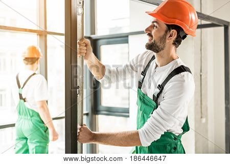 Concentrated constructor is using building ruler in order to check level of deviation. He standing near iron frame
