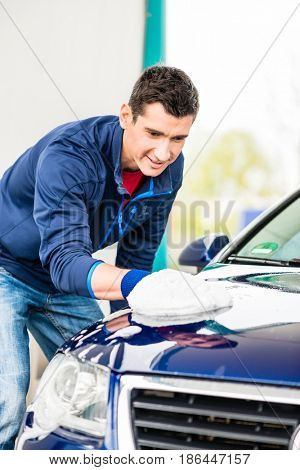 Hard-working young man polishing car with white microfiber mitt at auto wash