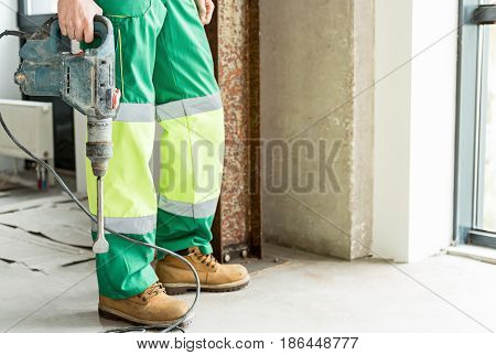 Builder wearing work clothes is holding big puncher. He standing near window. Focus on instrument. Close up of his legs