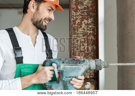 Cheerful builder is using puncher. He standing near wall and looking at instrument with smile. Profile