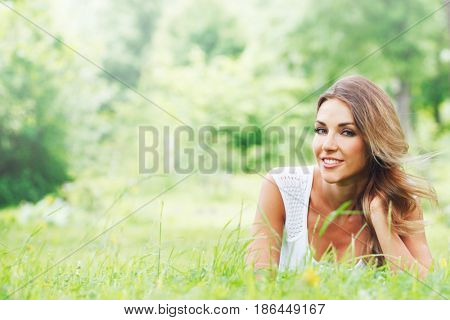 Beautiful young woman in white dress lying on grass