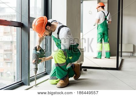 Concentrated builder is working with puncher. He squatting and looking down. His colleague standing near wall