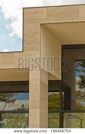 Building facade with elegant Birttish Portland Stone columns. The windows of the building reflecting the sky and trees