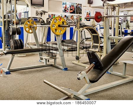 Fitness Room with jogging treadmill and Weight Machines. Group of treadmill in row big sport gym. Empty gym with sportsmen and sportswomen pictures on walls .
