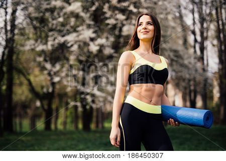 Fitness Girl With Yoga Mat Standing Outdoor In Nature - Fit Woman With Exercise Accessory In Summert