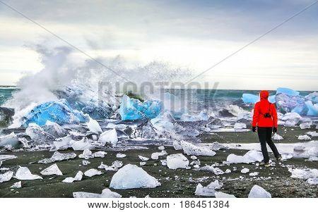 Woman Watching Waves Crash Against Icebergs At Jokulsarlon Glacial Lagoon Near Vatnajokull National