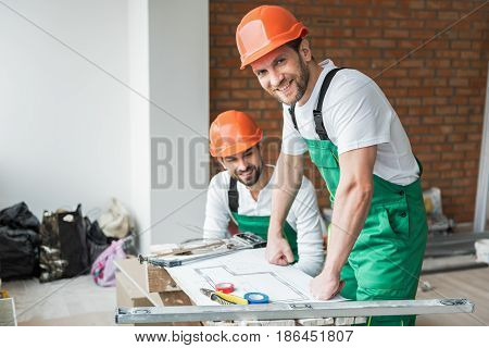 Cheerful bearded builder is inclining on table with necessary draft and looking at camera with smile. His brightly smiling coworker squatting. Portrait