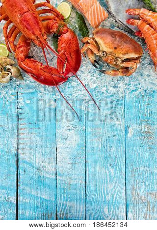Whole lobster with seafood, crab, mussels, prawns, fish, salmon steak and other shells served on crushed ice and wooden table