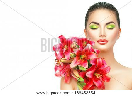 Beauty Girl with Lilly Flowers bouquet. Beautiful Spa Model woman with Blooming pink lily summer flowers. Skin care. Nature. Holiday Creative Makeup. Fashion Make up. Isolated on white Female Portrait