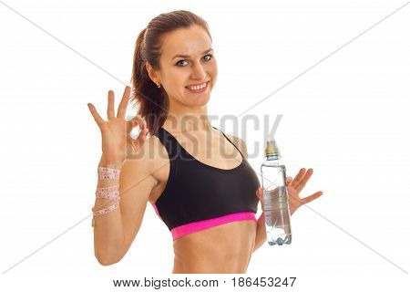 cutie young slim sports girl in uniform with bottle of water smiling on showing ok on camera isolated on white background