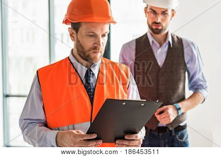 Serious builder is holding folder, his colleague standing behind him. They looking at documents with gravity