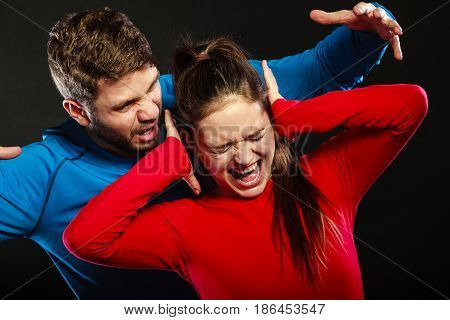 Husband abusing wife. Aggresive man screaming at crying scared woman. Domestic violence aggression. Bad relationship.