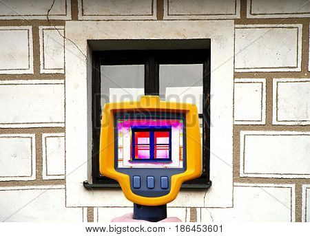 An infrared thermal imager showing building facade and window heat loss.