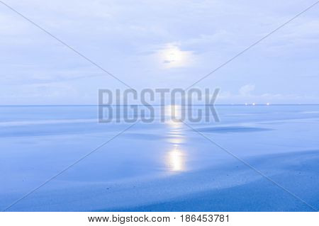 Beautiful coast sea with the moon at twilight morning / full moon in the sky in the early morning