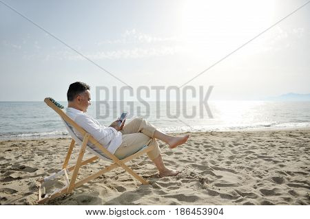 Man on holiday relaxing with tablet on the beach sitting on a deckchair
