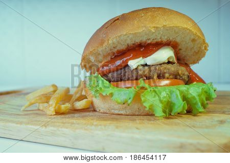 A traditional American burger with a chop, tomato and cheese on a salad leaf. French fries. fast food. close-up