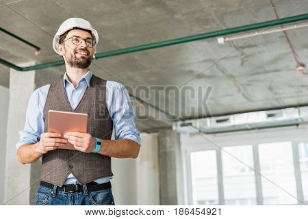 Happy builder is standing in wide room. He holding gadget and looking aside with smile. Low angle