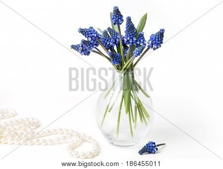 Bouquet of hyacinths in a transparent vase and pearl necklace on a white background. Space for text.