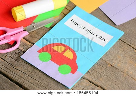 Happy Father's day greeting card. Colored paper sheets, scissors, glue on old wooden background. Creative Father's day cards for kids to make. Kids paper crafts idea. Closeup